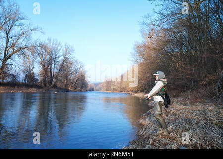 A young attractive woman catches fish with a spinning, standing on the bank of a river on a clear spring sunny day - Stock Image