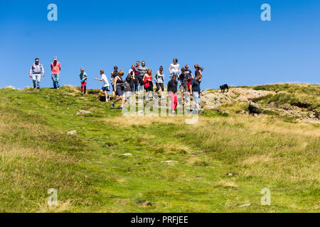 A group of young people and other walkers on the footpath leading south from the summit of  Cat Bells (451 metres) near Keswick, Cumbria. - Stock Image