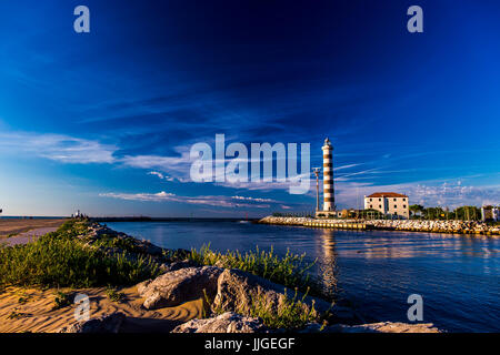View at the lighthouse in the bay with beach on the other side and beautiful blue sky. Sunrise time. Jesolo, Italy. - Stock Image