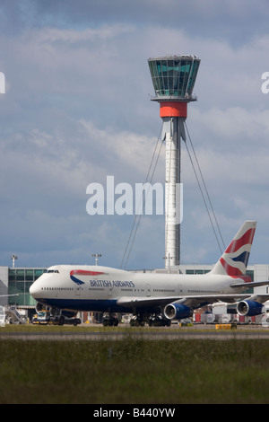 British Airways Boeing 747 taxiing in front of London Heathrow control tower. - Stock Image