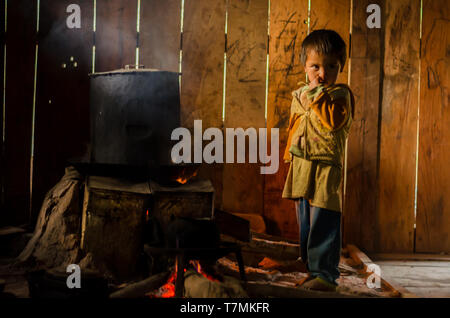 A boy in the kitchen of his house, Phongsali, Laos - Stock Image