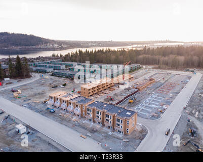 An aerial view of a townhouse complex and a new development under construction nearby in North Vancouver, BC - Stock Image