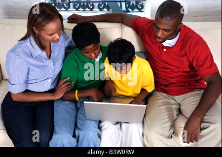 African American family staring at a laptop computer - Stock Image