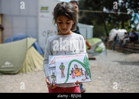 Dieses kurdische Mädchen will mir ihre tragische Geschichte anhand von Skizzen erzählen. Flüchtlingscamp von Idomeni in Griechenland an der Grenze nac - Stock Image