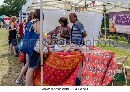 Visitors enjoying the sunshine at Fleet Food Festival 2018. Customers buying some of the local curry sauces and chutneys on offer. - Stock Image