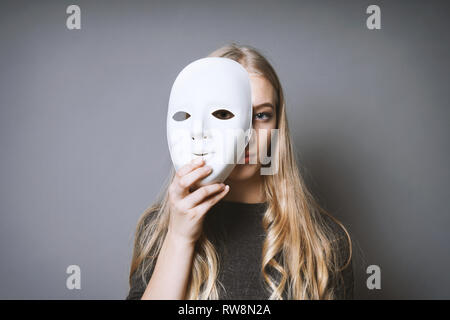 teen girl hiding her face behind mask - identity or personality concept - Stock Image
