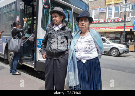 A couple that appear to be Mexican immigrants wait outside a tore on 82nd Street in Jackson Heights, Queens, New York City. - Stock Image
