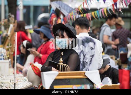 Woman wearing facial hygiene mask at a market stall in Shanghai, China - Stock Image