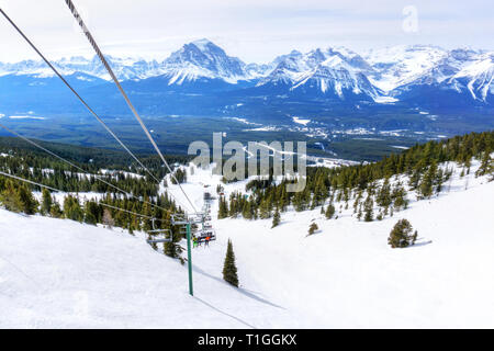 Unidentifiable skiers on chairlift going up a ski slope in the snowy mountain range of the Canadian Rockies. - Stock Image