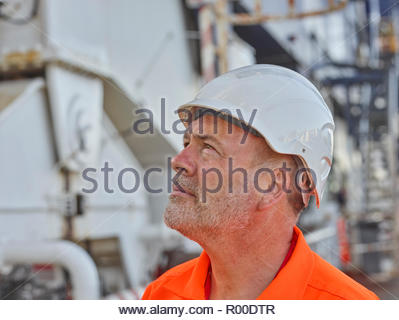 Dock worker with hardhat looking up - Stock Image