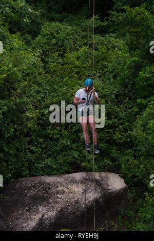 Man with a phone on zipline in Samui beach, Thailand - Stock Image