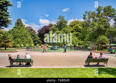 8 January 2019: Christchurch, New Zealand - People sitting and walking near the Peacock Fountain in Christchurch Botanic Gardens. - Stock Image