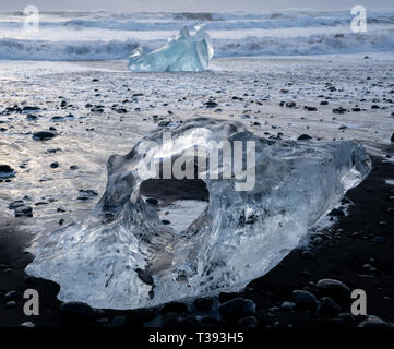 Icebergs at the black sand Diamond Beach with the sea in the background, Joekulsarlon, Iceland - Stock Image