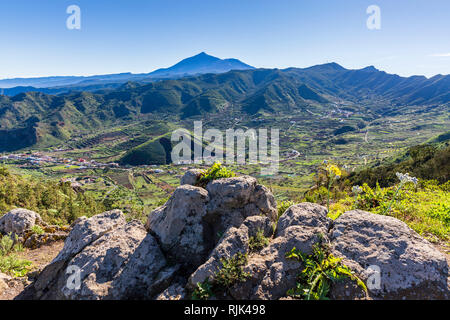 Looking down over the El Palmar valley and a hill dug out for topsoil, with mount Teide in the distance,  Teno, Tenerife, Canary Islands, Spain - Stock Image