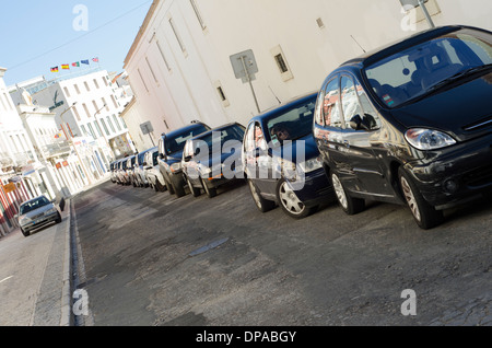 A diagonal line of cars parked along back street of white mediterranean buildings, with Hotel flags in the background. - Stock Image
