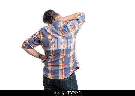 Hurting man with back to camera touching painful neck isolated on white studio background - Stock Image