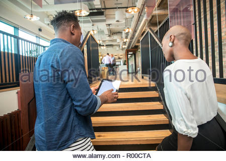 Colleagues using digital tablet on staircase - Stock Image