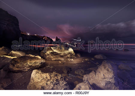 Rocks on beach at night in Portugal - Stock Image