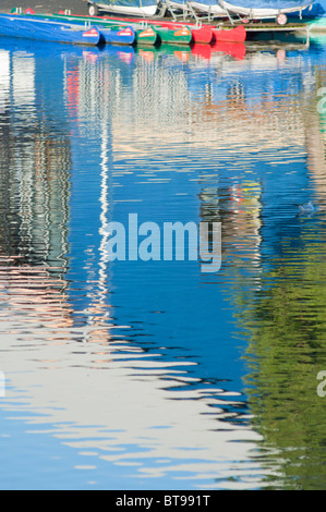Reflections of the Visitor centre/boathouse and boats at the Arrow valley lake country park Redditch, West Midlands, - Stock Image