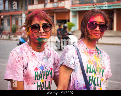 Two young Nepali girls covered with coloured powder after celebrating the Hindu festival Holi in Pokhara, Nepal - Stock Image