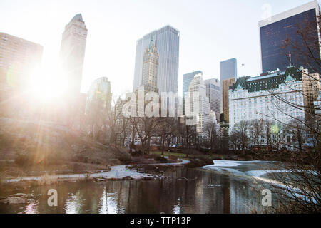 Lake by buildings in city on sunny day - Stock Image