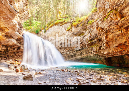 Morning sun peeks through the forest as a waterfall flows into Johnston Canyon creek at Banff National Park in Alberta, Canada. Johnston Canyon is a p - Stock Image