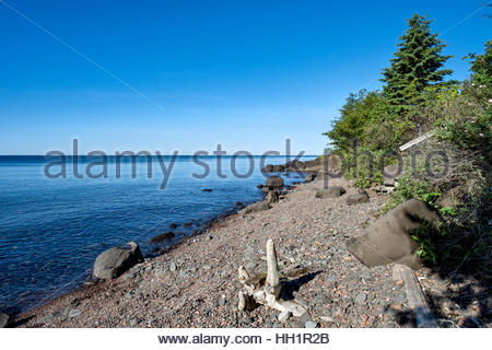 A stairway leads down to stony beach with driftwood, north shore of Lake Superior near Grand Marais, Minnesota. - Stock Image