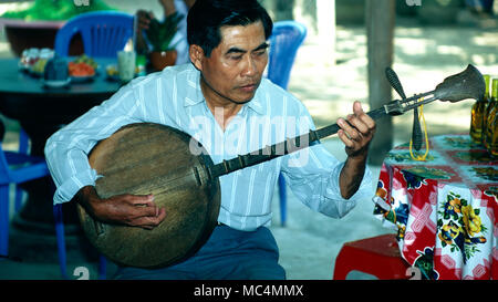 A Vietnamese man playing a traditional two-strined guitar. - Stock Image
