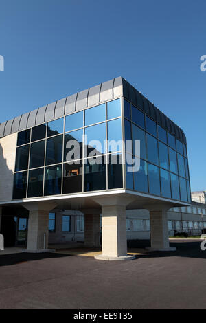 Glass fronted new building on pillars in courtyard on a bright sunny day - Stock Image