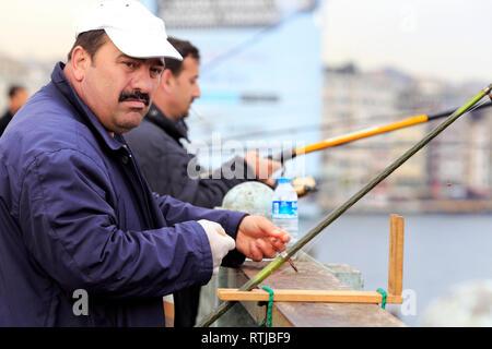 Fisherman on Galata Bridge, Bosphorus, Istanbul, Turkey - Stock Image