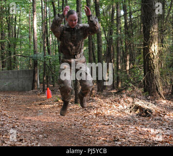 Sgt. Korey Wilson, assigned to 30th Medical Brigade, long jumps during an obstacle course for the 2018 21st Theater Sustainment Command Best Medic Competition Aug. 29, 2018 at Landstuhl, Germany. Day three of the Best Medic Competition tested Soldiers on day and night land navigation, an obstacle course, and a written exam. #21BMC2018 #FirstInSupport #StrongEurope #VictoryMedics (U.S. Army photo by Sgt. Benjamin Northcutt 21st Theater Sustainment Command) - Stock Image