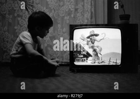 young boy sitting on floor watching cartoons on a vintage television set 1970s hungary - Stock Image
