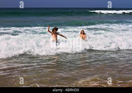 Two boys happily jumping in the cold waves of Marengo Beach in early spring, Australia. - Stock Image