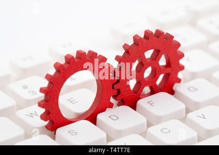 Two red gears on computer keyboard - Stock Image
