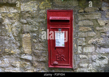 old red postbox displaying collection times and next collection built into a wall - Stock Image