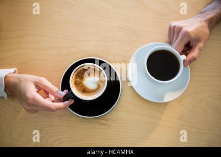 Hands of couple holding cup of coffee - Stock Image