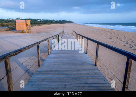 Looking down a straight wooden decking pathway with wooden railings on each side, the pathway is on a big sweeping sandy beach and leads onto pure san - Stock Image
