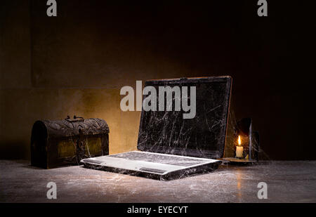 An old laptop covered in cobwebs. - Stock Image