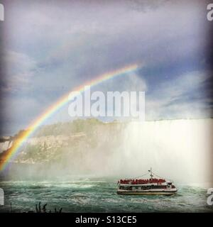 Niagara Falls and the Hornblower boat with a rainbow. - Stock Image