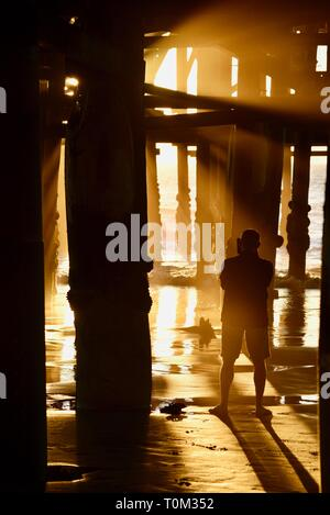 Middle age man taking photograph with mobile smart phone under Crystal Pier during sunset, with sun rays piercing the pier, San Diego, CA, USA - Stock Image