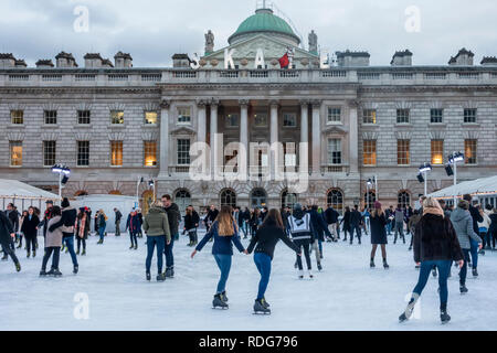 People (men and women) skating on the pop-up ice rink outside Somerset House in central London, England, UK. - Stock Image