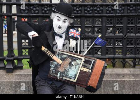 Westminster, London, UK. 27th Mar 2019. Remain Protester. A Charlie Chaplin actor 'smashes' a TV with a hammer marked Brexit. Houses of Parliament, Westminster, London. UK Credit: michael melia/Alamy Live News - Stock Image