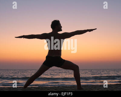 A man practicing yoga warrior pose on a beach - Stock Image