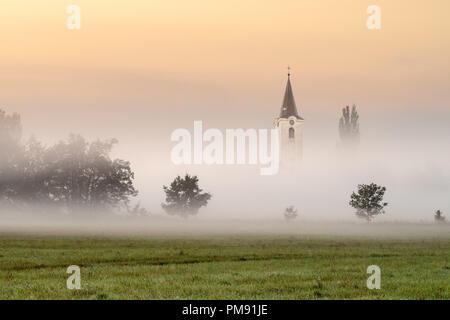 Small church in the fog. Morning haze by the sunrise. - Stock Image