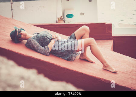 Beautiful young fashion caucasian woman laying and relaxing on a red wall - vacation and tourist concept with nice cute lady barefoot enjoying the out - Stock Image