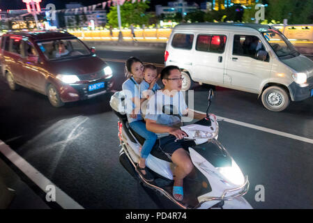 Family of mother, baby and father on motor scooter speed through city center on hot summer night, Libo, Guizhou Province, China. - Stock Image