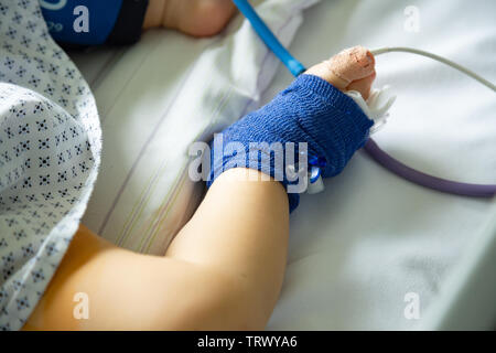 Foot of a sick child in hospital with peripheral venous line and pulse oximetry - Stock Image