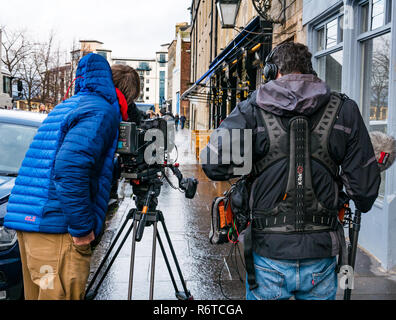 The Shore, Leith, Edinburgh, Scotland, United Kingdom, 6th December 2018. A film crew for BBC2 TV programme Inside the Factory due to be screened next Summer on the wet streets at the landing point of George IV's visit to Edinburgh for which Sir Walter Scott created a myth about tartan and Highland dress. The series is produced by Voltage TV and explores how a specific product is made.This episode is about the story of tartan - Stock Image