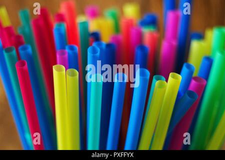 A collection of new plastic, disposable colored straws standing upright in a cup. - Stock Image