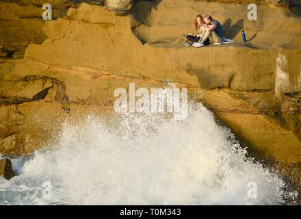 A young couple sitting above crashing waves to watch sunset, on the sandstone cliffs of Sunset Cliffs, San Diego, CA, USA - Stock Image
